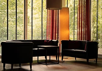 Black leather armchair beside brown window curtain
