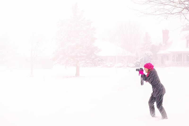 Woman wearing black coat white holding camera in the middle of snow storm