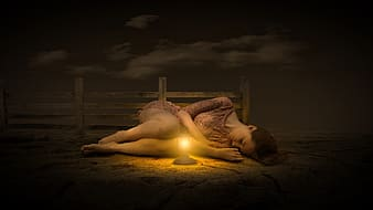 Woman lying on sand during sunset