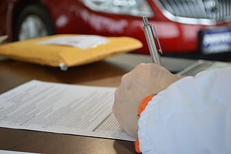 Person writing on paper on top of table