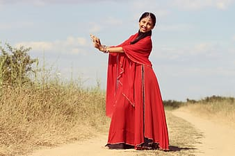 Woman wearing red tradition dress nearby brown grass