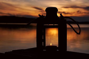 Black fire pit on brown wooden dock during sunset