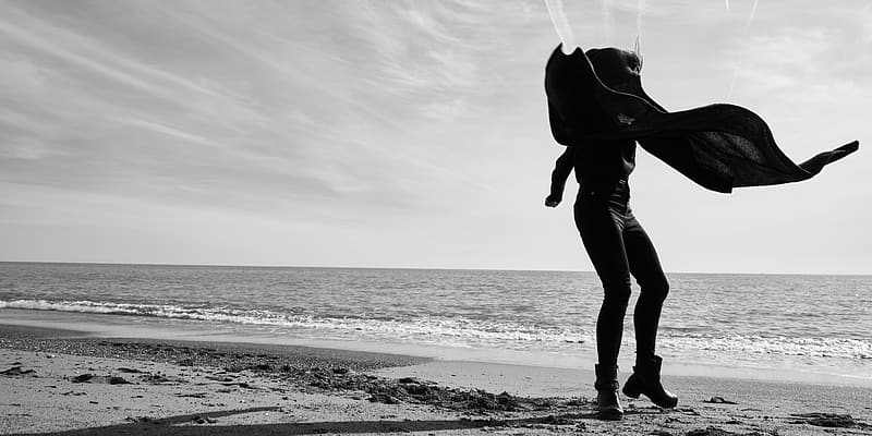 Grayscale photo of person in black pants and black jacket standing on beach shore
