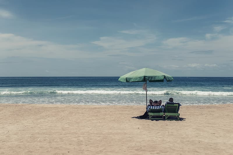 Two people resting by the beach