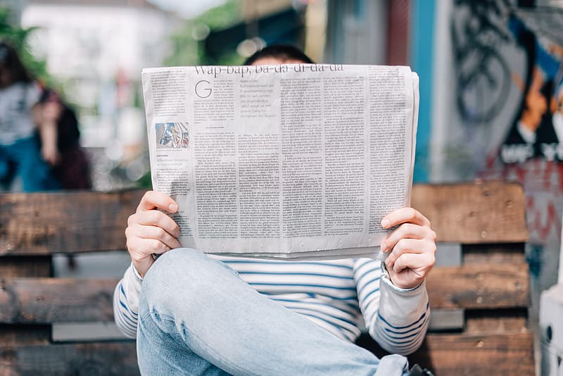 Person holding newspaper while sitting on bench