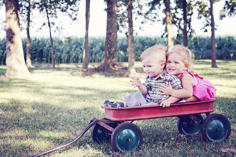 Boy and girl riding on pull wagon photograph