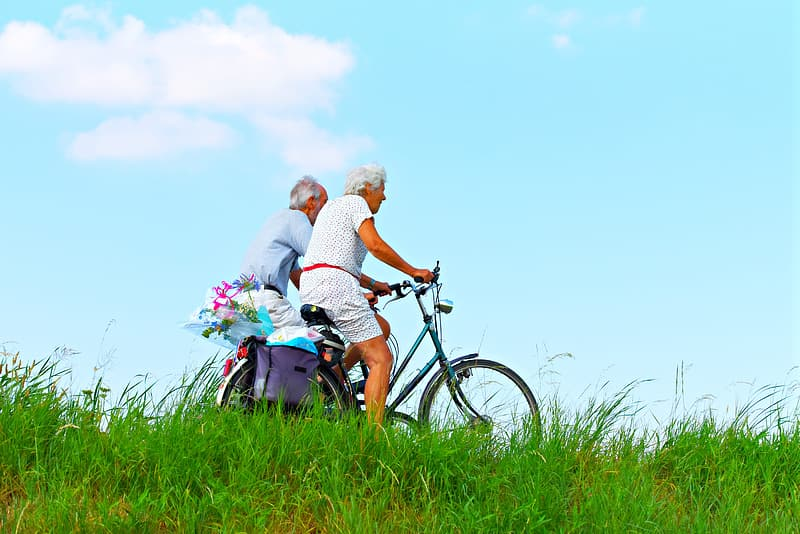 Man and woman riding on bicycle on green grass field during daytime