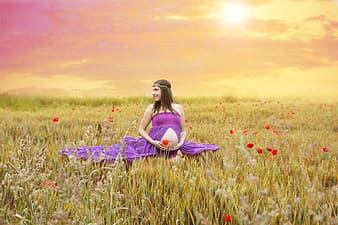 Pregnant woman in purple dress sitting on green grass field during daytime
