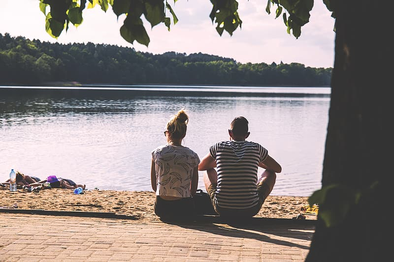 Couple sitting on concrete floor front of body of water