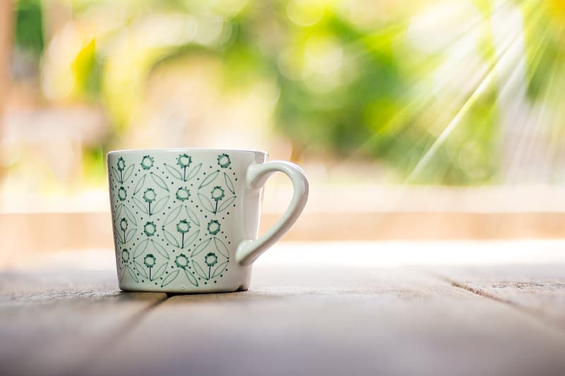 White and green ceramic teacup on brown wooden surface
