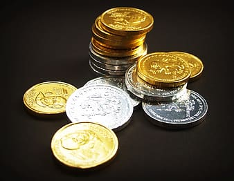 Assorted round gold-colored and silver-colored coins on black surface