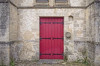 Gray brick structure with red wooden door