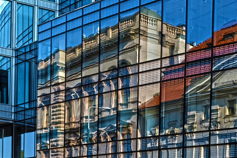 Clear curtain wall building with a reflection of gray concrete building taken during daytime