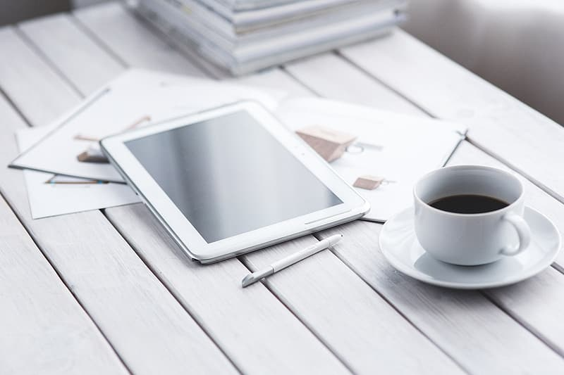 White tablet computer beside white ceramic teacup
