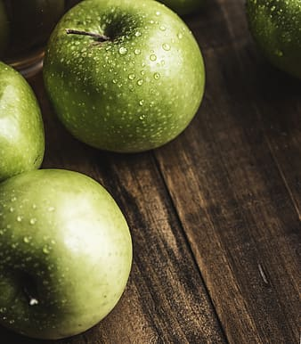 Photo of green apples on brown wooden surface