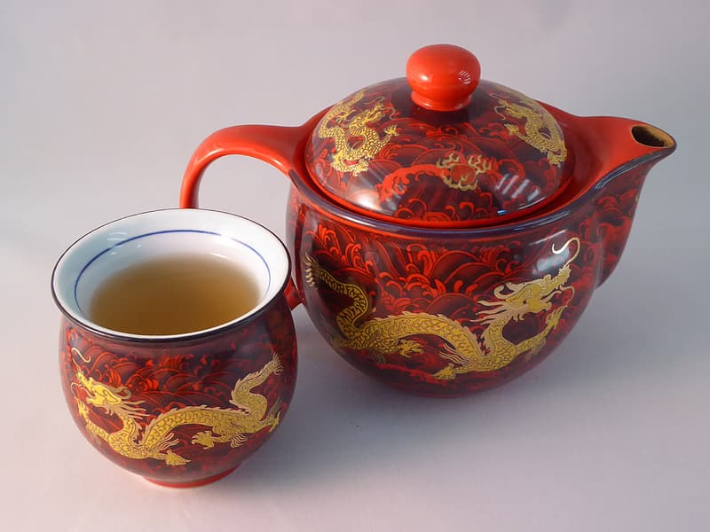 Red and brown dragon print teacup beside teapot