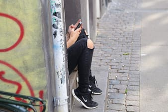 Shallow focus photography of person wearing distressed black jeans using smartphone