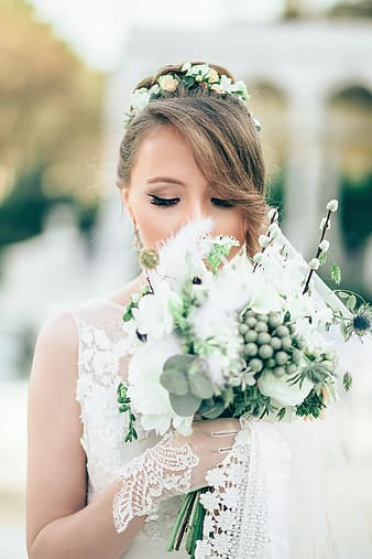 Closed-up photo of bride smelling bouquet