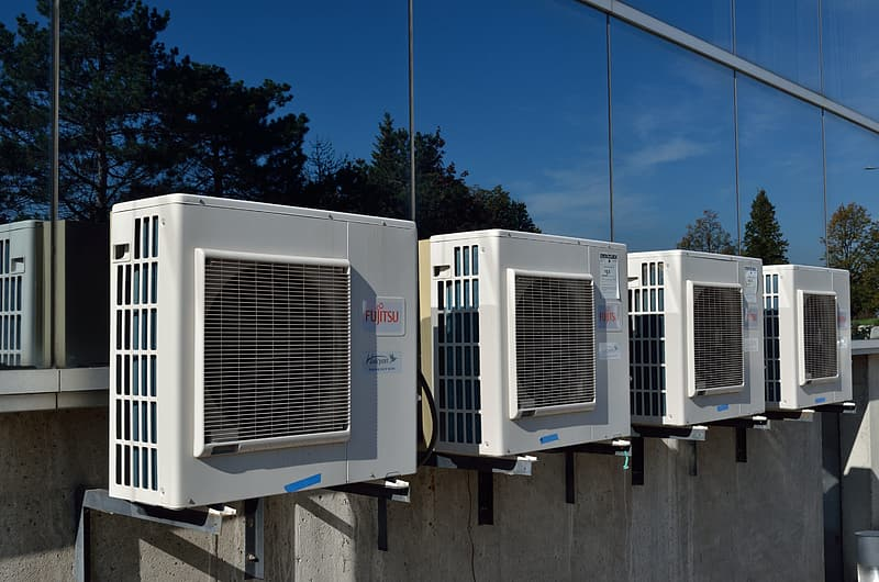 Four white air condensers outside building