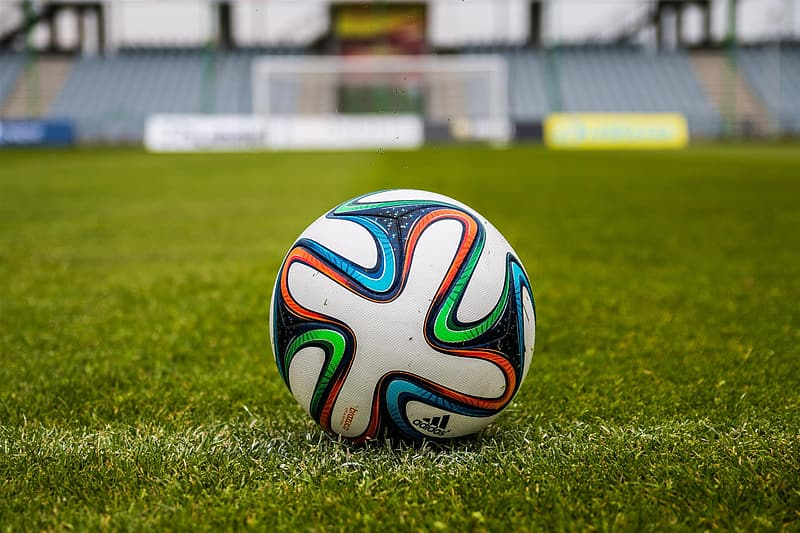 White blue and red soccer ball on green grass field during daytime