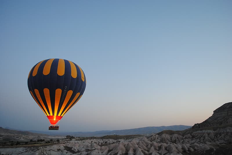 Blue and yellow hot air balloon hovering above mountain