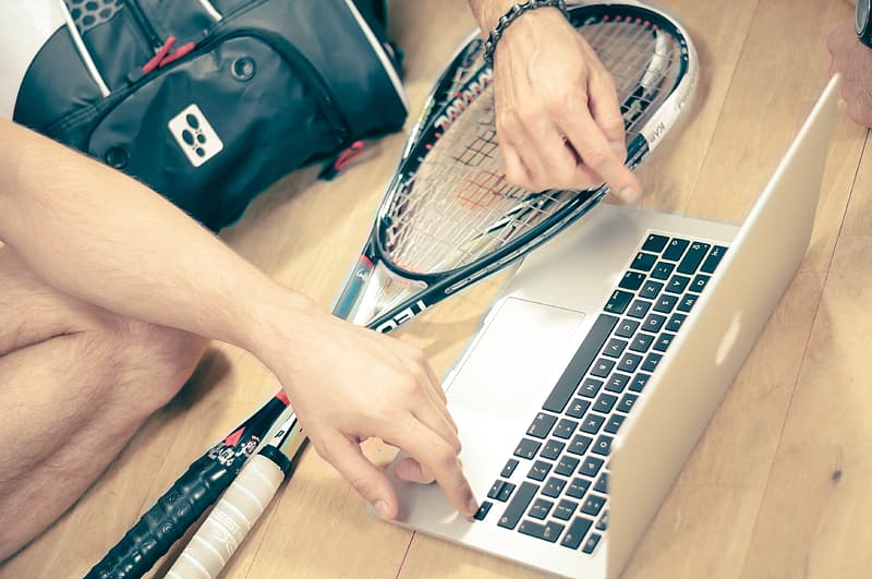 Person holding black and white tennis racket