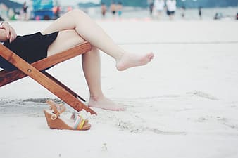 Woman in black bikini sitting on brown wooden chair on white sand during daytime