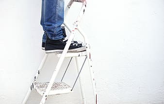 Person standing on a frame ladder
