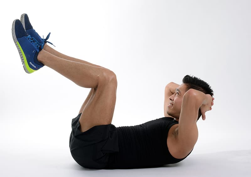 Man wearing black tank-top doing exercise on the floor