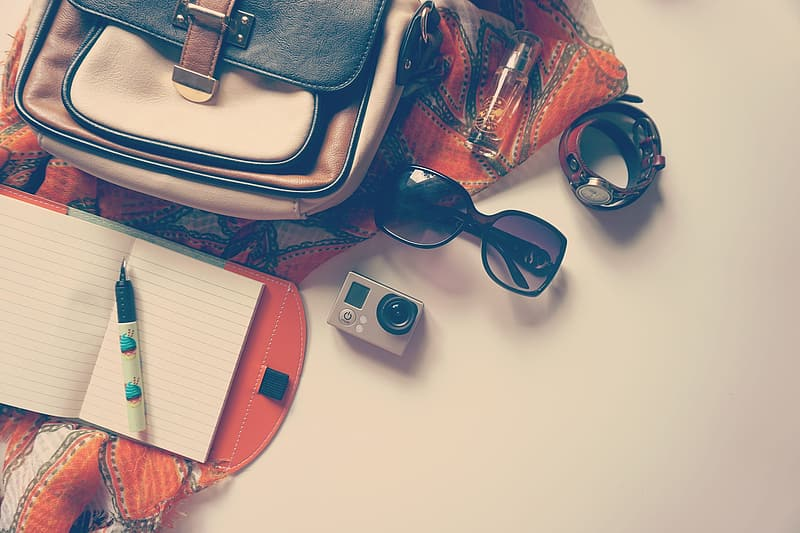 Black framed sunglasses beside red leather bag and silver iphone 6