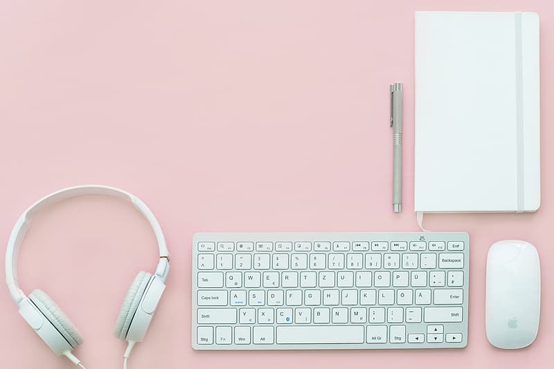 Photography of Apple Magic Keyboard between Magic Mouse and corded headphones under pen and book
