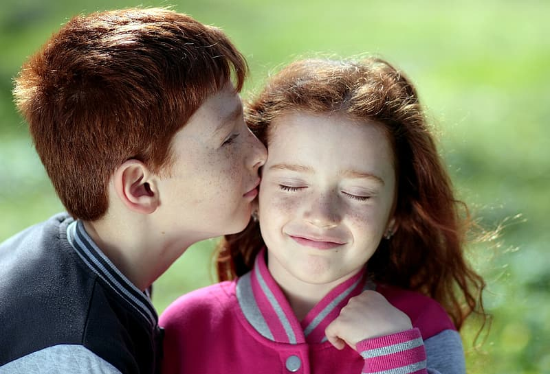Boy kissing girl in shallow focus photography