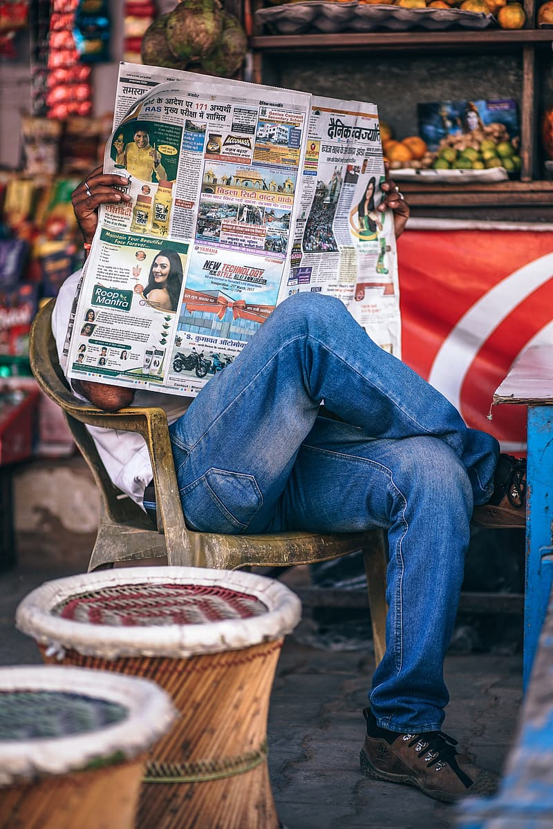 Person in blue denim jeans sitting on brown wooden chair reading newspaper