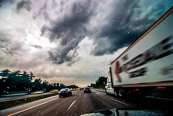 Cars on road under cloudy sky during daytime