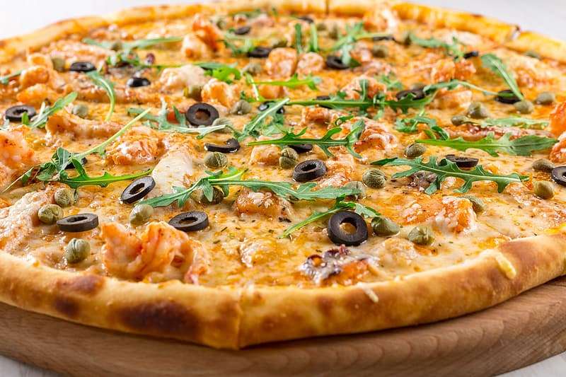 Pizza with olives and green leaves