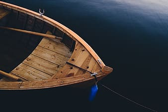 Brown wooden sailing boat with paddle