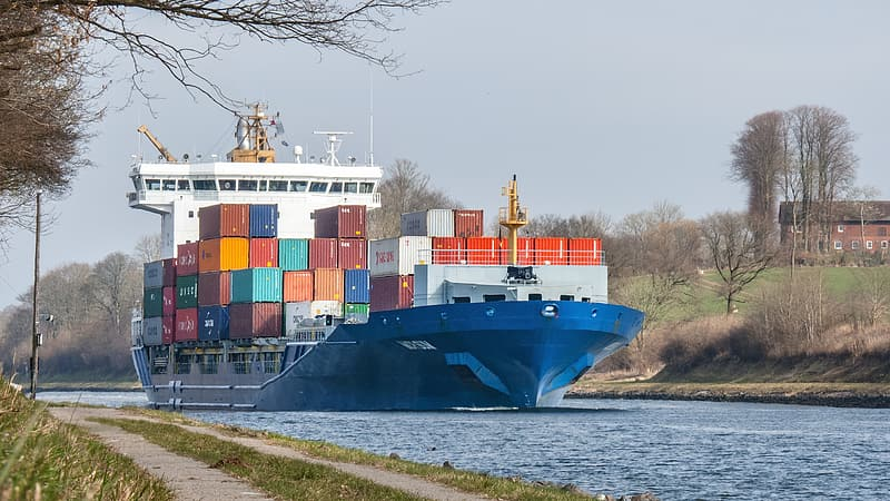Blue and white cargo ship on dock during daytime