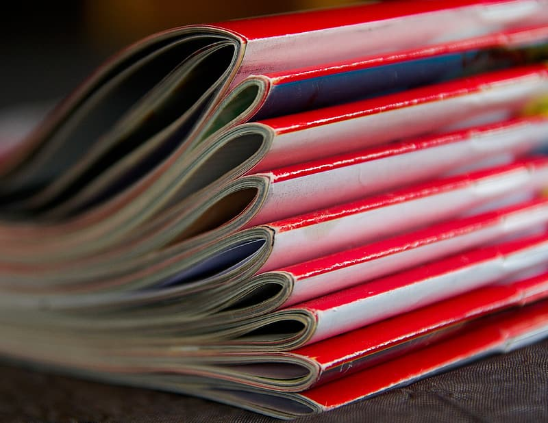 Selective focus photography piled red magazine books
