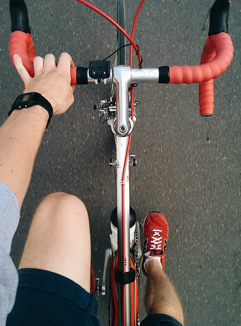 Person wearing red New Balance shoes riding on road bicycle