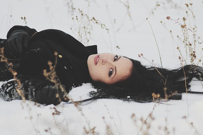 Woman in black jacket lying on snow covered ground