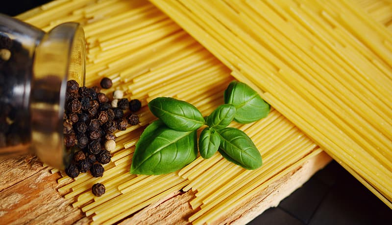 Green leaves on top of uncooked pasta
