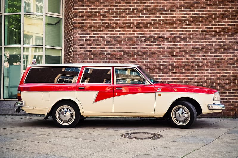 White and red vintage car parked beside brown brick wall