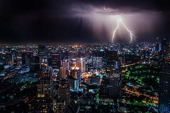 Lightning over city buildings during night time