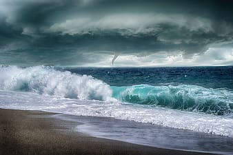 Ocean waves crashing on shore under cloudy sky during daytime