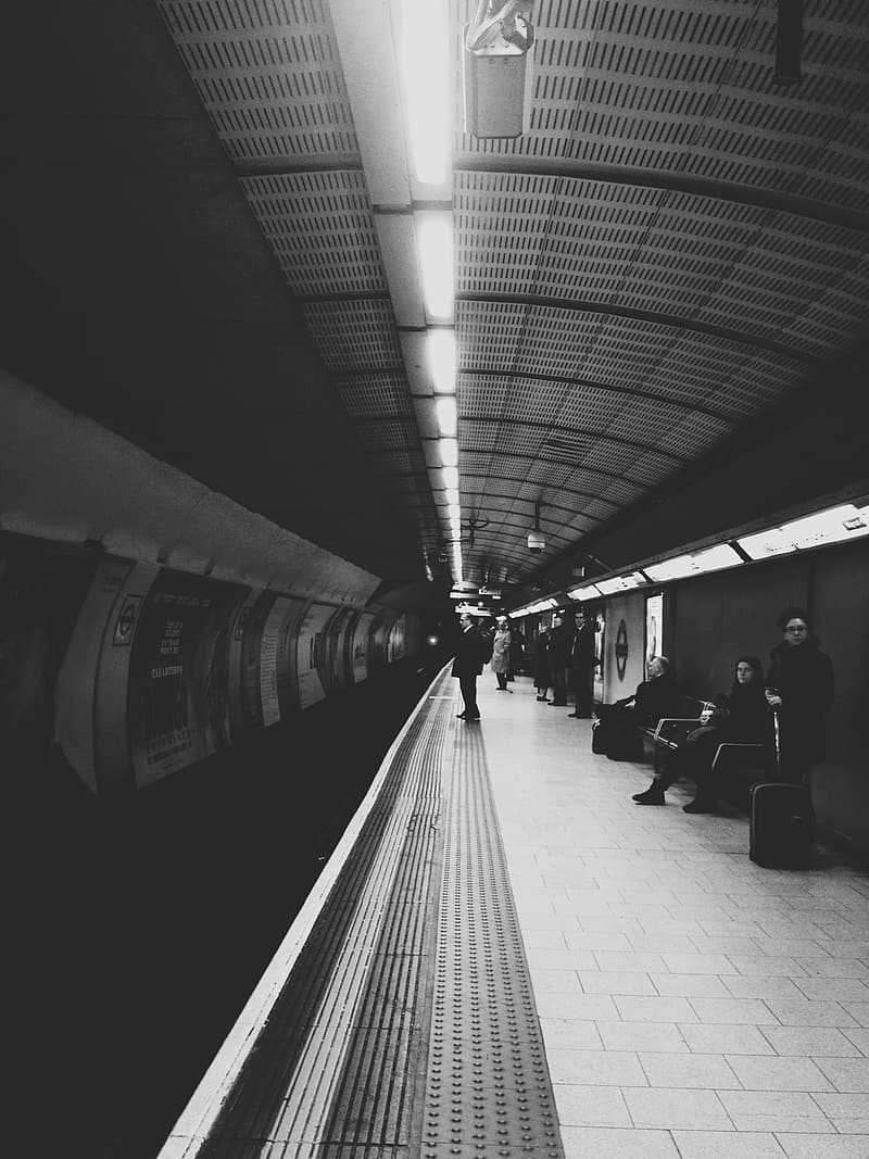 Grayscale photograph of person standing on train station