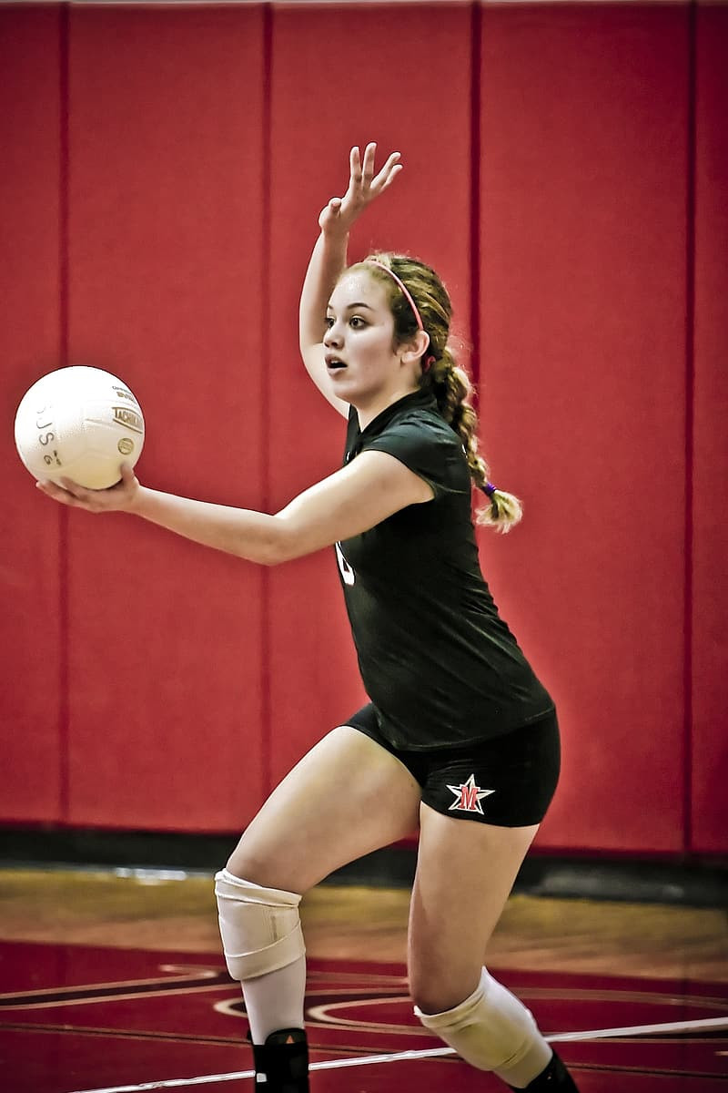 Woman serving volleyball ball inside room