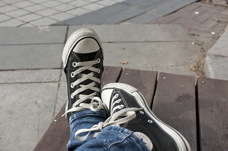 Person in blue denim jeans and black and white converse all star high top sneakers