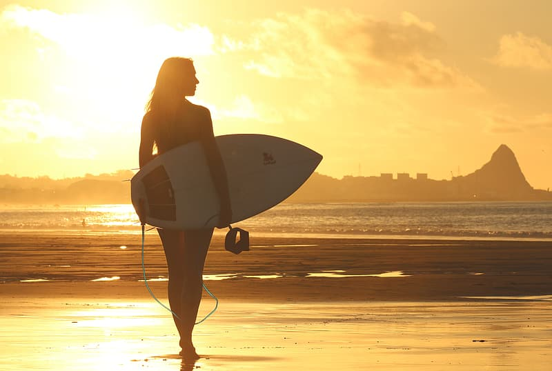 Silhouette photography of woman holding surfboard