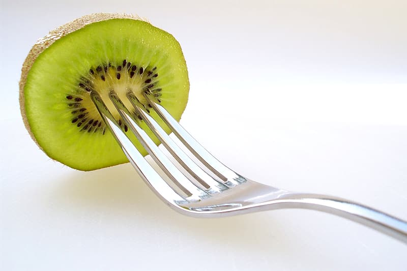 Stainless steel fork with sliced kiwi fruit