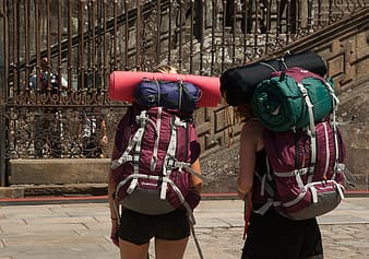 Two person carrying hiking backpack and mats